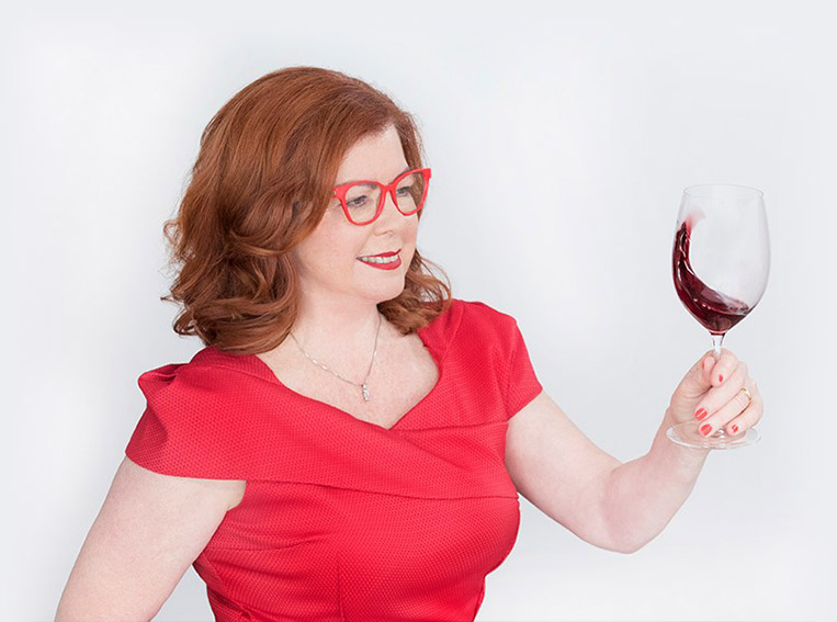 Virginia Jacobs wearing red glasses and red dress, holding glass of wine